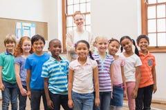 微笑对照相机的老师和学生在教室 库存照片