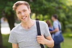 微笑对照相机的英俊的学生外面在校园里 免版税库存照片