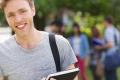 微笑对照相机的英俊的学生外面在校园里 免版税库存图片