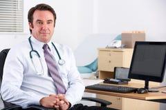 微笑对照相机的英国医生坐在他的服务台 库存图片