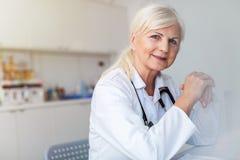微笑对照相机的资深女性医生 免版税库存照片