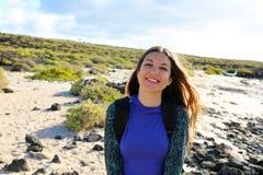 微笑对照相机的远足者女孩户外 探索兰萨罗特岛小山和海滩的愉快的年轻旅客妇女在一个晴朗和大风天 库存照片