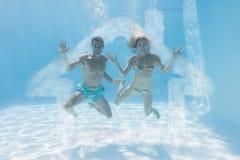 微笑对照相机的逗人喜爱的夫妇的综合图象在水面下在游泳池 库存图片