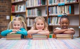 微笑对照相机的逗人喜爱的学生在图书馆里 库存照片