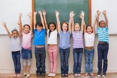 微笑对照相机的逗人喜爱的学生在教室 免版税图库摄影
