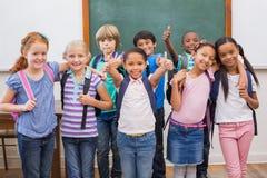 微笑对照相机的逗人喜爱的学生在教室 免版税库存照片