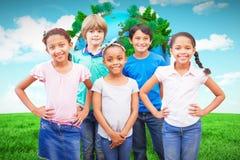 微笑对照相机的逗人喜爱的学生的综合图象在教室 图库摄影