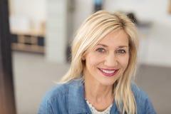 微笑对照相机的长发白肤金发的妇女 免版税库存照片