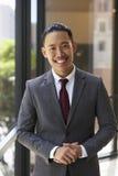 微笑对照相机的年轻亚洲商人,垂直 免版税库存图片