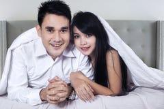 微笑对照相机的年轻夫妇在旅馆卧室 库存照片