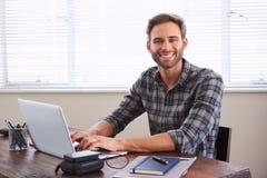 微笑对照相机的年轻男学生,当工作在任务时 库存照片