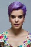 微笑对照相机的紫罗兰色短发妇女 图库摄影