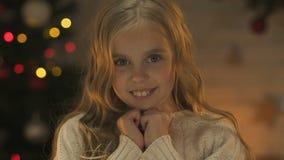 微笑对照相机,在圣诞节,特写镜头的等待的奇迹的愉快的逗人喜爱的女孩 影视素材