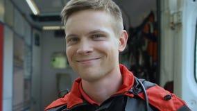 微笑对照相机,在背景,急救的救护车的友好的男性医务人员 影视素材