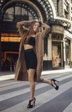 微笑对街道的滑稽的愉快的时兴的女孩 免版税库存图片