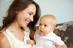微笑对逗人喜爱的婴孩的一个愉快的母亲的画象 免版税图库摄影