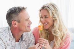 微笑对给了她一朵玫瑰的伙伴的愉快的妇女 库存图片