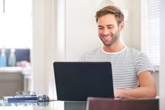 微笑对他的膝上型计算机屏幕的可爱的人在家坐 图库摄影
