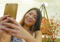 微笑年轻俏丽和愉快的亚裔韩国旅游的妇女拿着拍自画象selfie照片的手机户外在bea 库存图片