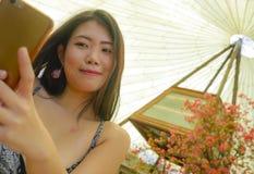 微笑年轻俏丽和愉快的亚裔韩国旅游的妇女拿着拍自画象selfie照片的手机户外在bea 免版税库存图片