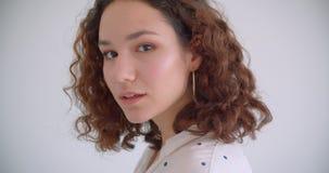 微笑年轻俏丽的卷曲白种人的女性特写镜头射击愉快地修理她的看照相机有背景的头发 股票视频