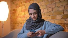 微笑年轻可爱的回教的女性使用电话和看照相机特写镜头射击hijab的,当坐时 股票录像