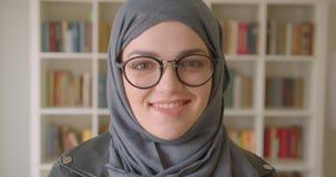 微笑年轻可爱的回教的女生和玻璃特写镜头画象hijab的愉快地看在的照相机 影视素材