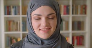 微笑年轻可爱的回教的女生特写镜头画象hijab的愉快地看照相机在学院 股票视频
