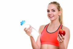 微笑年轻愉快的十几岁的女孩,当拿着水瓶和时 免版税库存图片