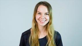 微笑年轻美丽的逗人喜爱的快乐的女孩看在白色背景的照相机 图库摄影