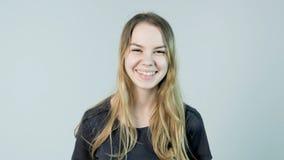 微笑年轻美丽的逗人喜爱的快乐的女孩看在白色背景的照相机 库存图片