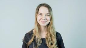 微笑年轻美丽的逗人喜爱的快乐的女孩看在白色背景的照相机 免版税库存照片