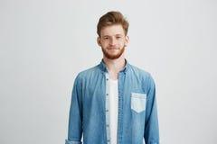 微笑年轻英俊的人画象斜纹布衬衣的看在白色背景的照相机 图库摄影
