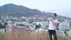 微笑年轻英俊的旅游的人,当采取在小山时的selfie 股票视频