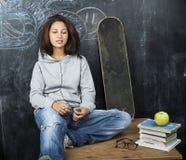 微笑年轻逗人喜爱的十几岁的女孩在黑板就座的教室在桌上,现代学生行家概念,生活方式 免版税图库摄影