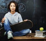 微笑年轻逗人喜爱的十几岁的女孩在黑板就座的教室在桌上,现代行家概念 免版税图库摄影