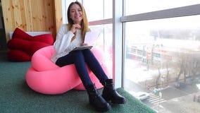 微笑并且显示姿态在照相机可爱的少妇的画象,在咖啡馆的软的扶手椅子坐在全景附近 影视素材