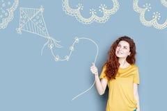 微笑快乐的学生,当飞行在夏令营时的一只风筝 免版税图库摄影