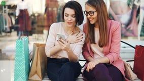 微笑快乐的年轻女人在购物使用一起看屏幕的智能手机和笑的基于长凳 影视素材