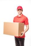 微笑快乐的送货人愉快的年轻的传讯者拿着纸板箱和,当站立在白色背景时 免版税库存图片