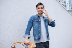 微笑快乐的年轻的人谈话在手机和,当站立在他的自行车附近时 免版税库存图片