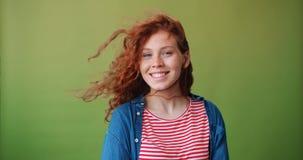 微笑悦目的女孩画象有飞行头发的看照相机 股票录像