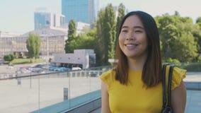 微笑愉快的亚裔企业的女孩,当走时 股票视频