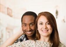 微笑愉快的人种间夫妇的特写愉快地摆在和,拿着男朋友的妇女朝向用她的手,白色演播室 免版税库存照片