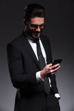 微笑愉快的商人,当发短信时 库存照片