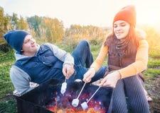 微笑愉快的夫妇和在营火的烘烤蛋白软糖在自然 快乐的男人和妇女休息在火 免版税图库摄影