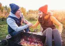 微笑愉快的夫妇和在营火的烘烤蛋白软糖在自然 快乐的男人和妇女休息在火 免版税库存照片