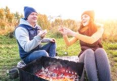 微笑愉快的夫妇和在营火的烘烤蛋白软糖在自然 快乐的男人和妇女休息在火 免版税库存图片