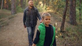 微笑愉快的孩子的慢动作远足与他的父亲在狂放的森林里和享受室外活动和自然 股票录像