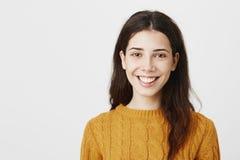 微笑愉快的年轻欧洲的妇女特写镜头画象广泛地佩带的黄色毛线衣和身分在灰色背景 库存照片